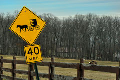 Amish häst- och barnvagnvägmärke i förgrund med hästar som betar i bakgrunden fotografering för bildbyråer