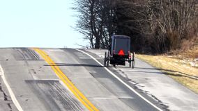 A Amish Horse and Buggy on a highway stock footage