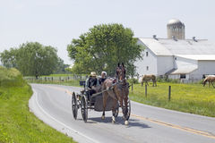 Amish horse and carriage. Driving past barn in Lancaster County, Pennsylvania Stock Photo