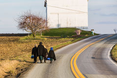 Amish people walking up rural road in Lancaster County PA. With barn in background Royalty Free Stock Image
