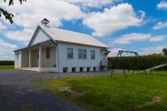 Amish skolahus med gungor Arkivfoto