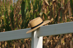 Amish straw hat laying over fence post with corn field in the ba Stock Photography