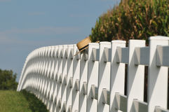 Amish straw hat laying over fence post Royalty Free Stock Image