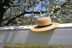 Amish straw hat on a white fence stock photo