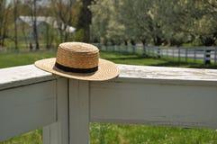 Amish sugrörhatt på ett vitt staket arkivbild
