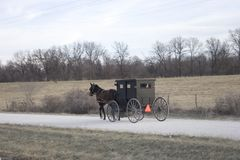 Amish Transportation. A panned motion shot of a amish buggy traveling down a gravel road Stock Photos