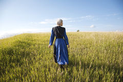 Amish woman in blue dress and black cape in field. An Old Order Amish woman in a blue dress and black cape and apron walks in a grassy field on a sunny afternoon Royalty Free Stock Photography