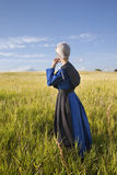 Amish woman standing in grassy field with afternoon sunlight Stock Photos