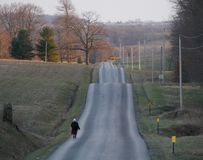 Amish woman on a wavy road. An Amish woman walks along a wavy road in Eastern Ohio Royalty Free Stock Photography
