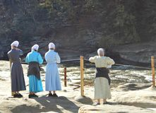 Amish women on vacation. Four Amish women with their backs to you standing looking over a waterfall and stream behind a roped off area in a park stock images