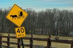 Amishpaard en verkeersteken Met fouten in voorgrond met paarden die op de achtergrond weiden stock afbeelding