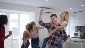 Amistad, baile alegre de la gente joven y diversión el tener en el partido de casa que disfruta de vacaciones divertidas almacen de metraje de vídeo