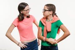 Amistad de dos adolescentes En el fondo blanco, las muchachas hablan y ríen Imágenes de archivo libres de regalías