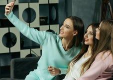 amistad, gente y concepto de la tecnología - amigos o adolescentes felices con el smartphone que toma el selfie en casa Imágenes de archivo libres de regalías