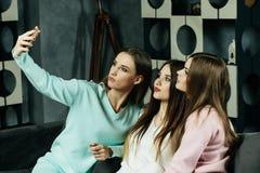 amistad, gente y concepto de la tecnología - amigos o adolescentes felices con el smartphone que toma el selfie en casa Foto de archivo libre de regalías