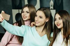 amistad, gente y concepto de la tecnología - amigos o adolescentes felices con el smartphone que toma el selfie en casa Imagen de archivo libre de regalías