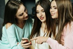Amistad, gente y concepto de la tecnología - amigos o adolescentes felices con smartphone en casa Imagenes de archivo