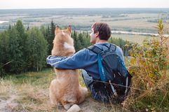 Amistad, hombre y perro sentándose junto en la montaña Fotos de archivo libres de regalías