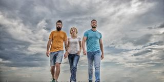 Amistad probada por a?os Amigos verdaderos unidos del threesome Fondo dram?tico del cielo nublado de los hombres y de los paseos  imágenes de archivo libres de regalías