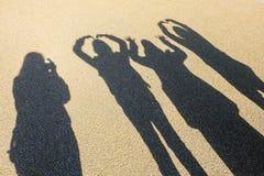 Amistad refleja de la sombra en la arena Imagen de archivo