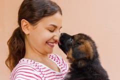 Amistad verdadera entre la muchacha y el perrito que está dando un beso imagen de archivo libre de regalías