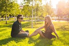 Amistad y concepto del amor con un par joven que se sienta en la hierba y hablar Imagenes de archivo