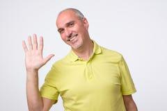 Amistoso-mirada del hombre europeo atractivo que renuncia la mano en hola gesto mientras que sonríe alegre imagen de archivo