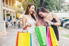 Amitié asiatique heureuse de femmes appréciant dépensant des paniers dedans Images libres de droits