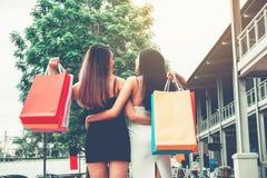 Amitié asiatique heureuse de femmes appréciant dépensant des paniers dedans Image stock