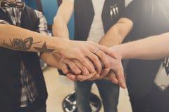 Amitié d'hommes Mains unies de jeune équipe avec le tatouage Photographie stock libre de droits