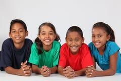 Amitié de quatre écoliers ethniques heureux Photos stock