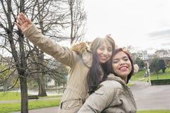 Amitié de sourire de la femme deux dans l'effet de contre-jour du soleil de parc Photos libres de droits