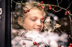 Amitié entre la fille et le chat derrière la fenêtre Image stock