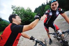 Amitié et course sur le vélo de montagne Photographie stock libre de droits