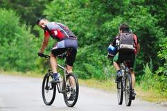 Amitié et course sur le vélo de montagne Photo stock