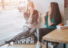 Amitié et technologie Deux jolies filles à l'aide des smartphones tout en buvant du thé ou du café au café Images libres de droits