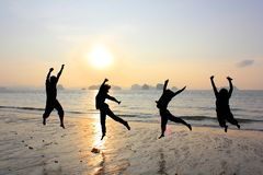 Amitié heureuse sautant à la plage photo stock