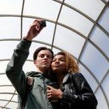 Amitié internationale d'une belle jeune fille noire et d'un type blanc Les étudiants enamourés prennent des photos d'eux-mêmes Image stock