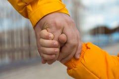 Amitié L'enfant tenant la main de l'homme haut étroit de photo Image stock