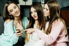 Amitié, les gens et concept de technologie - amis ou adolescentes heureux avec le smartphone au hom Images stock