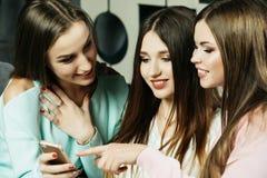 Amitié, les gens et concept de technologie - amis ou adolescentes heureux avec le smartphone au hom Image stock