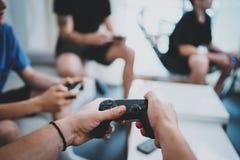 Amitié, technologie, jeux et concept de détente de temps à la maison - fermez-vous des amis masculins jouant des jeux vidéo à la  Images libres de droits