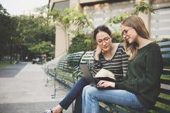 Amitié de femmes étudiant le concept de technologie de séance de réflexion Photo stock