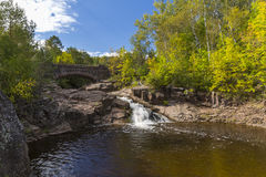 Amity Creek Bridge & Falls. A waterfall on a creek with a stone arch bridge in early autumn Stock Image
