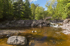 Amity Creek Bridge & Falls. A waterfall on a creek with a stone arch bridge in early autumn Royalty Free Stock Image
