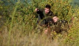 Amizade de caçadores dos homens Caçadores do homem com arma do rifle Boot Camp Forma uniforme militar Forças do exército camuflar fotografia de stock