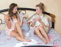 Amizade - duas meninas de sorriso têm a bisbolhetice, branca Fotografia de Stock