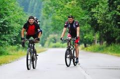 Amizade e curso na bicicleta de montanha foto de stock