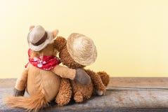 A amizade, urso de peluche que guarda o cavalo do luxuoso em seus braços, tonificou o vintage fotografia de stock royalty free