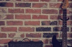 Amlifier e chitarra contro il muro di mattoni immagini stock libere da diritti